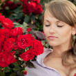 Young woman in flower garden smelling red roses — Stock Photo