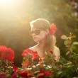 Young woman in flower garden smelling red roses #1 — Stock Photo