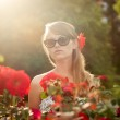 Young woman in flower garden smelling red roses #3 — Stock Photo