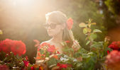 Young woman in flower garden smelling red roses #2 — Stock Photo