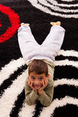Boy lying on the carpet — Stock Photo