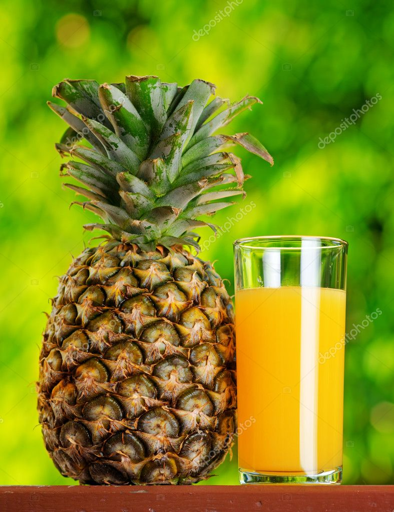 Glass of pineapple juice in a garden. — Stock Photo #11925343