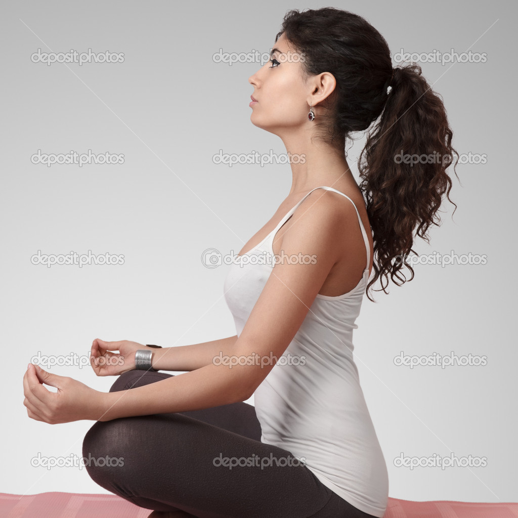 Beautiful young woman doing yoga exercise on mat  Stock Photo #11921827