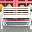 Foto Stock: White wooden bench in front of public fantacy door.