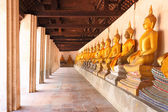 Row and pillar golden statue of Buddha in shade of church. — Stock Photo