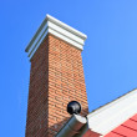 Orange brick pipe and black roof on blue sky — Stock Photo