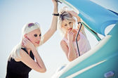 Two blonde girls stand by the broken car — Stock Photo