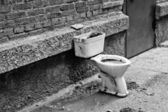 Old dirty toilet in the yard. Black and white — Stok fotoğraf