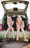 Two beautiful blonde girls sitting in trunk of broken car — Stock Photo