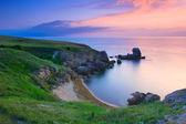 Amazing rocky coastline at sunset with the island — Stock Photo