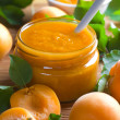 Apricot jam in jar and fresh fruits with leaves — Stock Photo
