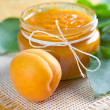 Apricot jam in jar and fresh fruit with leaves - Stock fotografie