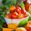 Apricots and sweet cherry with leaves — Stock Photo
