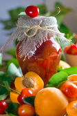 Apricot and sweet cherry confiture in jar and fresh fruits with leaves — Stock Photo