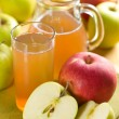 Apple juice and fresh fruits with leaves — Stock Photo