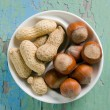 Peanuts and hazelnuts on vintage wooden surface. — Stock Photo #11432161
