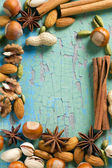 Aroma spices frame. Cinnamon, anise, peanuts, almonds, cardamom, hazelnuts on the vintage wooden surface. — Stock Photo