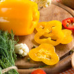 čerstvé žluté a červené Pepřenka na dřevěné desce — Stock fotografie