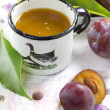Plum juice and fresh fruits with leaves — 图库照片