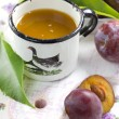 Plum juice and fresh fruits with leaves — Stockfoto
