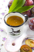 Plum juice and fresh fruits with leaves — Stock Photo
