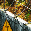 Sign on barbed wire security fence - Photo
