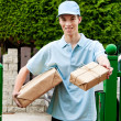 Stock Photo: Young mfrom package courier brings