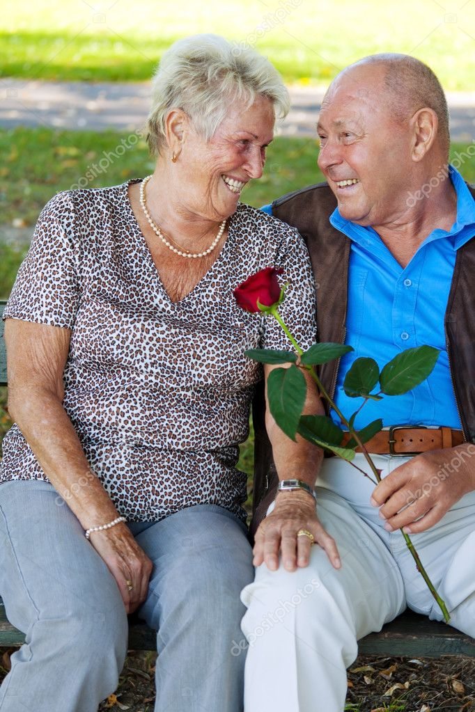 Older elderly couple in love. man gives a rose. — Stock Photo #10986586
