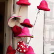 Red hats in front of a millinery — Stock Photo