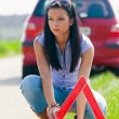 Woman with a warning triangle in case of breakdown — Stock Photo