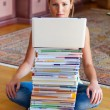 Student with a stack of books and computers — Stock Photo