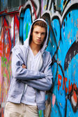 Cool-looking young man in front of graffiti — Stock Photo
