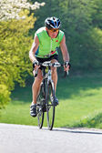 Senior riding a bicycle on a road bike — Stock Photo