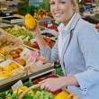Woman at the fruit market with shopping basket - Stock Photo