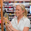 Woman at the wine shelf of a supermarket — Stock Photo