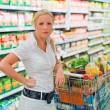 Woman with shopping cart in the supermarket — Stock Photo #11657767