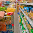 Woman with shopping cart in the supermarket — Stock Photo #11809299