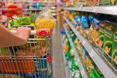 Femme avec panier d'achat dans le supermarché — Photo