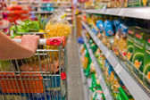 Woman with shopping cart in the supermarket — Stok fotoğraf