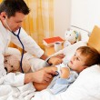 Stock Photo: Doctor house call. examines sick child.
