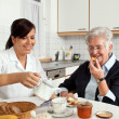 Stock Photo: Nurse helps elderly womat breakfast