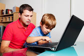 Man and child with laptop computer in home. — Stock Photo