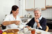 Enfermera ayuda a una anciana en el desayuno — Foto de Stock