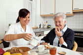 Nurse helps elderly woman at breakfast — Stok fotoğraf
