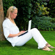 Womwith laptop computer in garden — Stock Photo #11888339