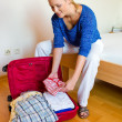 Woman pack your bags for vacation travel - Stock Photo
