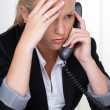 Frustrated womholding telephone in office — Stock Photo #11888525