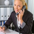 Stock Photo: Womwith telephone in office