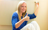 Woman sits in front of radiators — Stock Photo
