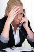 Frustrated woman holding a telephone in the office — Stock Photo
